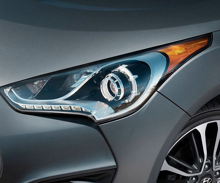 Close-up shot of Hyundai Veloster Turbo 2016 projector headlights with LED accents