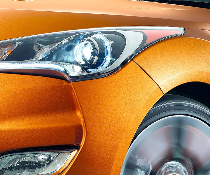 Exterior close-up photo of orange Hyundai Veloster 2016 hatchback projector headlights with LED accents