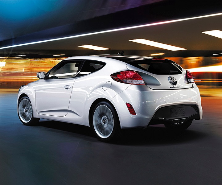 Exterior action photo of white Hyundai Veloster 2016 three door hatchback with sleek rear lights