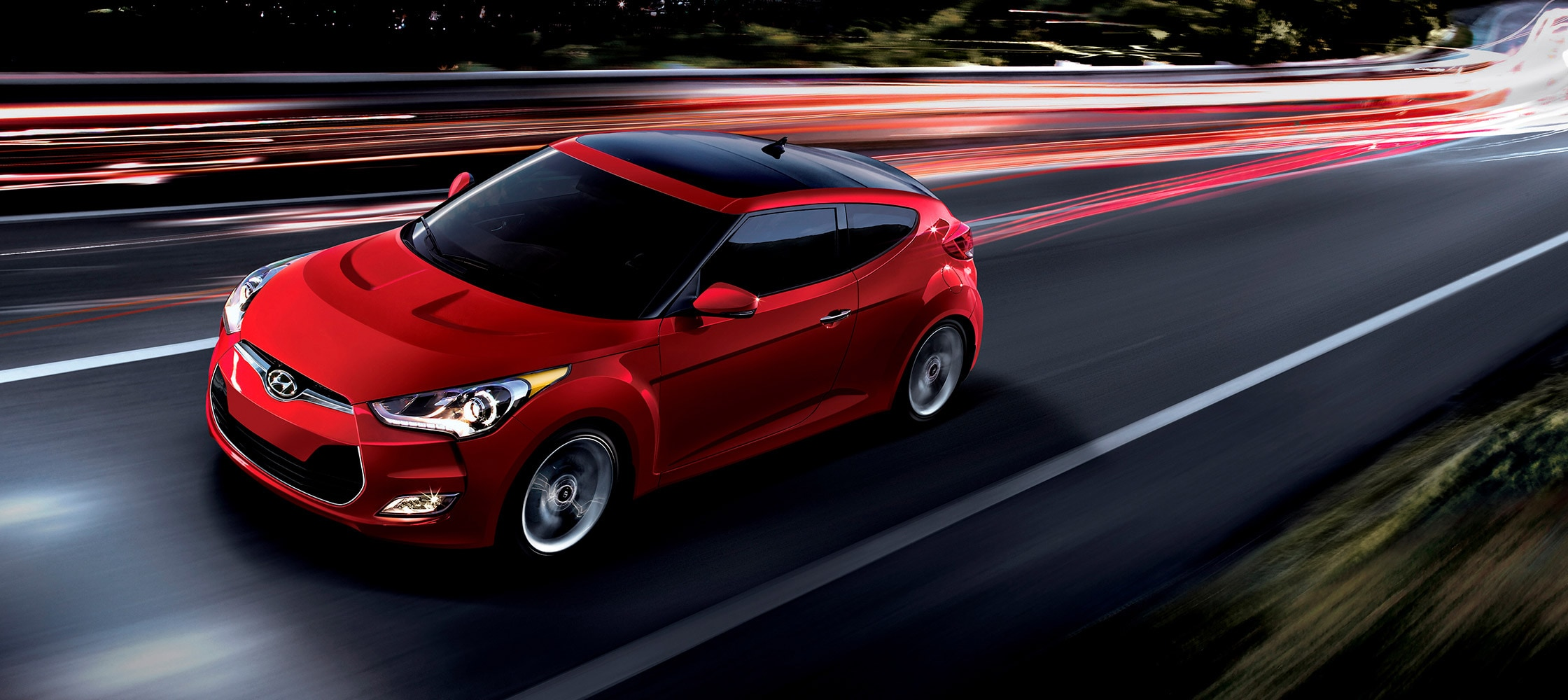 Exterior action photo of red Hyundai Veloster 2016 three door hatchback with large panoramic sunroof