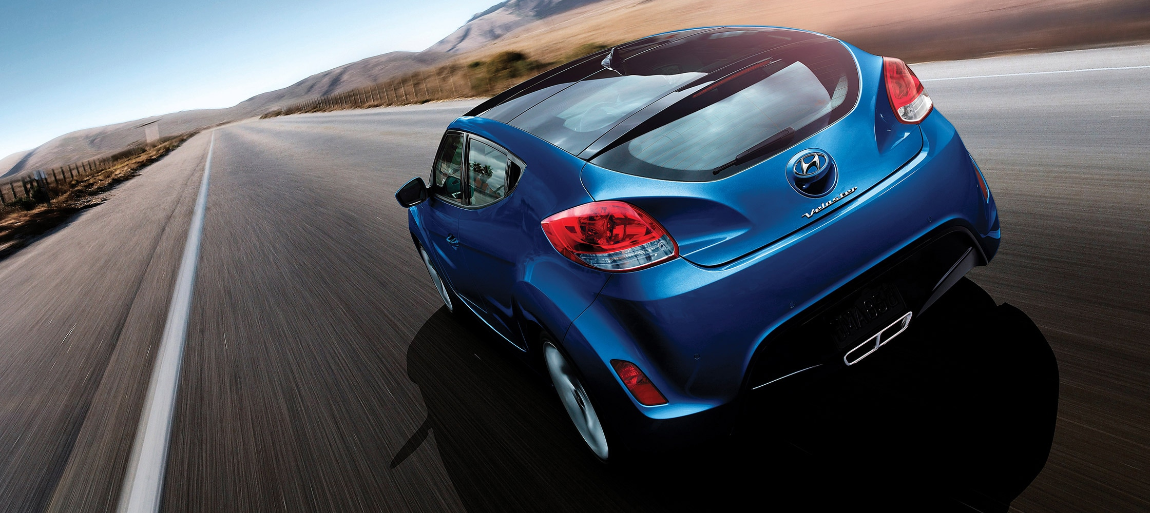 Exterior action photo of blue Hyundai Veloster 2016 three door hatchback with sleek rear lights