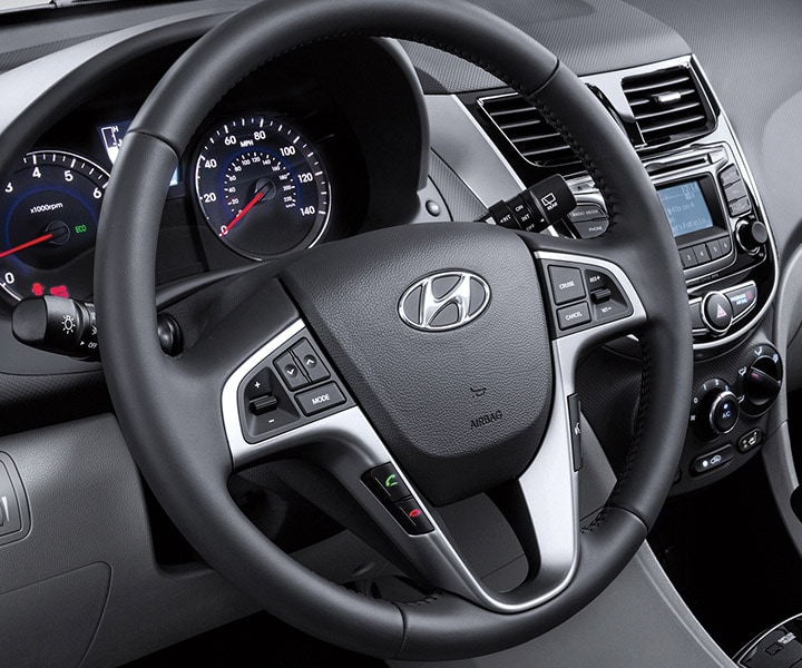 Interior photo of Hyundai Accent Sedan 2017 steering wheel-mounted controls to navigate personal playlists.
