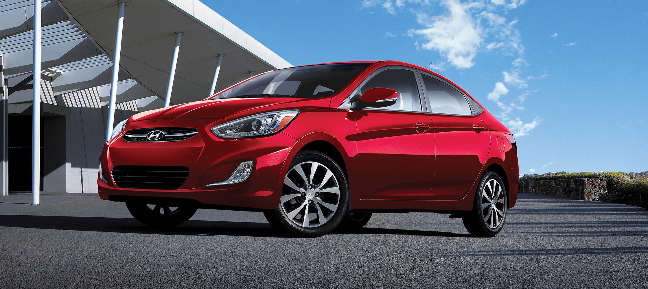 Exterior side picture of red Hyundai Accent Sedan 2017 in daylight