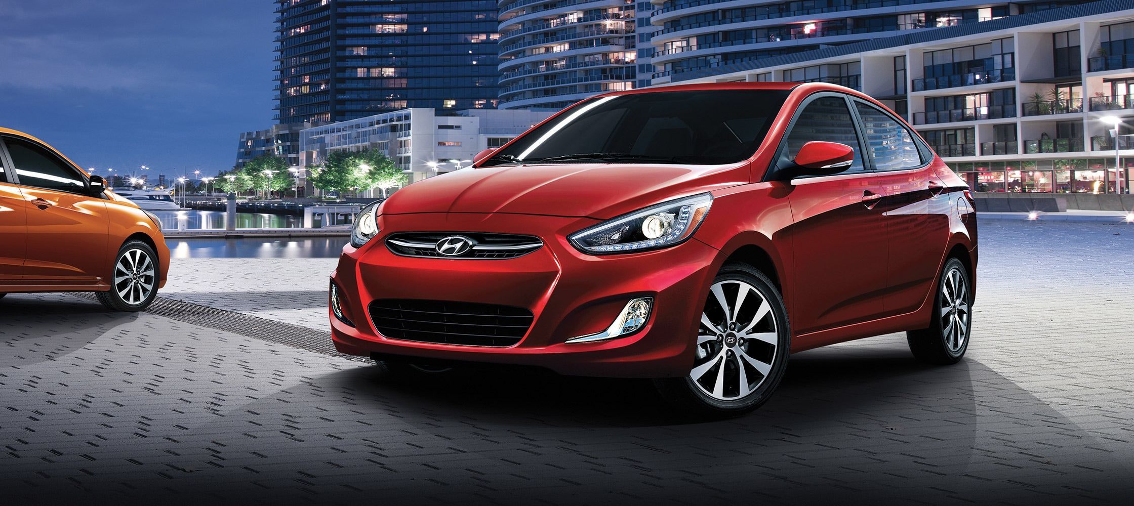 Exterior side picture of red Hyundai Accent Sedan 2017 at night