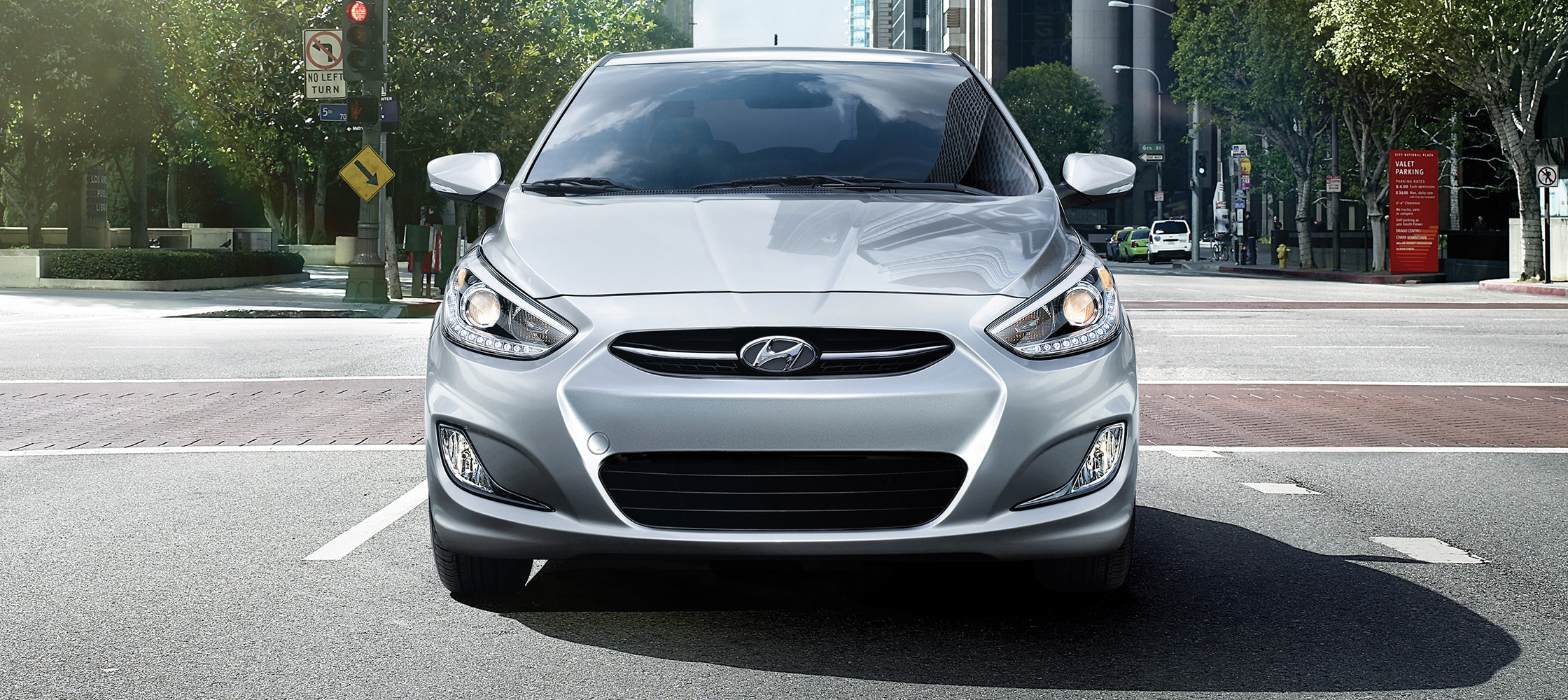 Exterior front photo of Grey Hyundai Accent Sedan 2017 driving on road