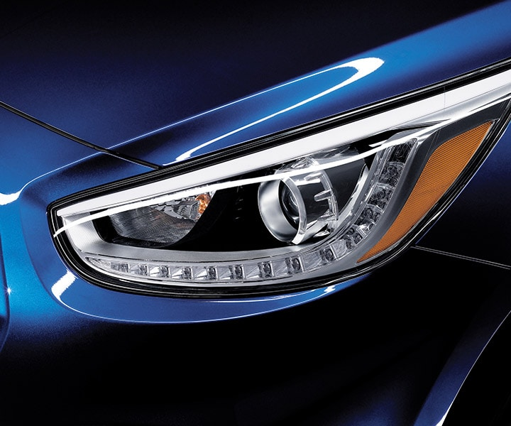Blue Hyundai Accent hatchback 2017 close up view of projection headlights with LED daytime running lights