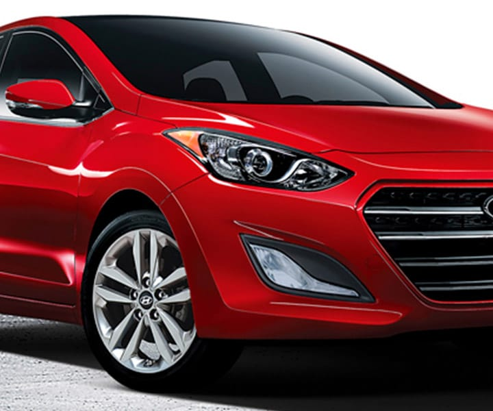 Exterior action shot of red Hyundai Elantra GT four door compact car with signature hexagonal grille
