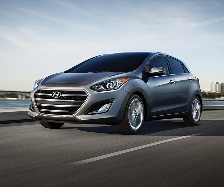 Exterior action photo of silver Hyundai Elantra GT four door compact car with signature hexagonal grille