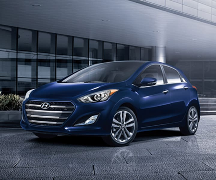 Exterior photo of blue Hyundai Elantra GT four door compact car with signature hexagonal grille