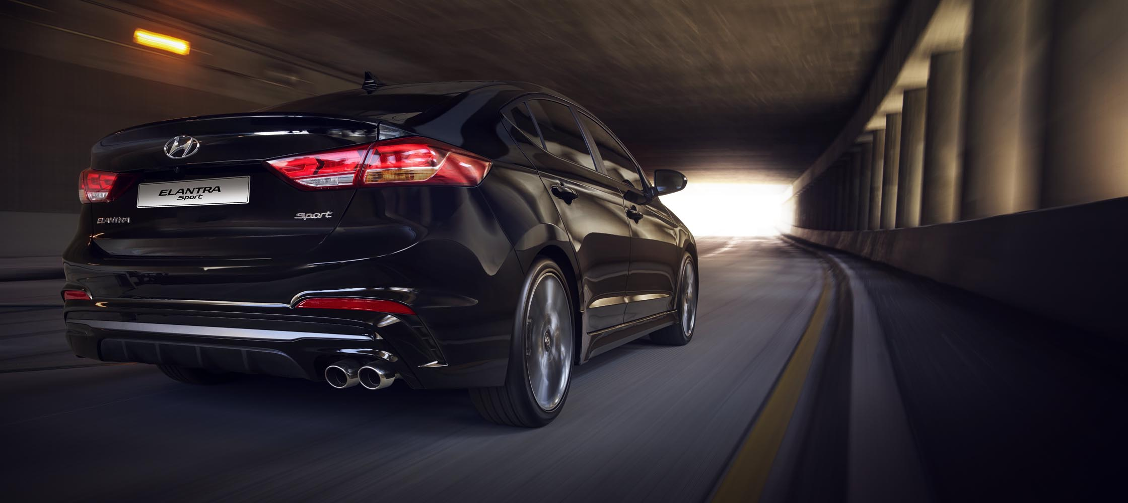 Back view of black Hyundai Elantra Sport 2017 with sleek rear lights, driving through a tunnel