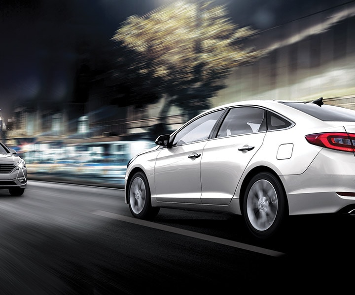 Exterior image of silver Hyundai Sonata Hybrid 2017 using high beam assistance against upcoming traffic