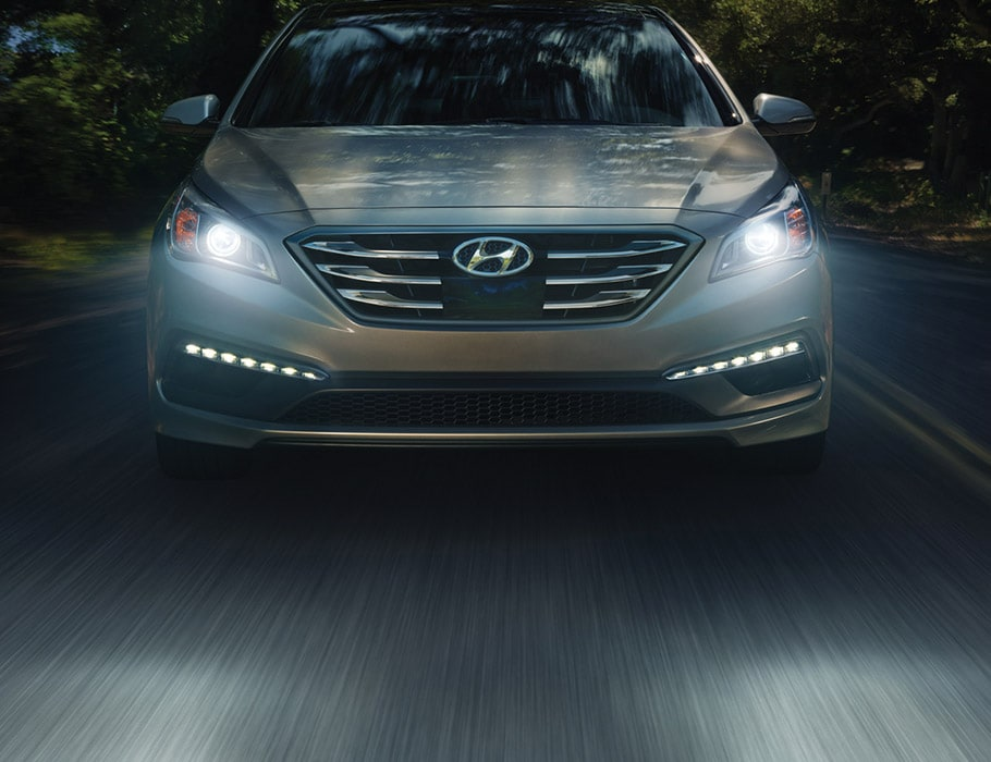 Exterior action shot of silver Hyundai Sonata 2017 four door sedan driving through a forest