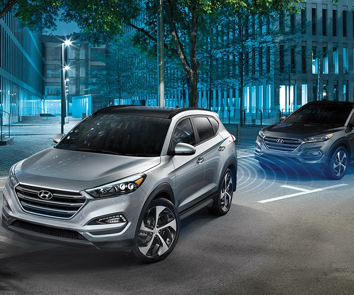 Exterior action photo of silver Hyundai Tucson 2017 CUV parallel parking with assistant sensors