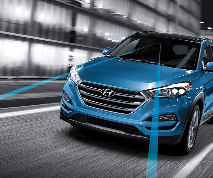 Exterior action photo of blue Hyundai Tucson 2017 CUV using blind spot detection to change lanes