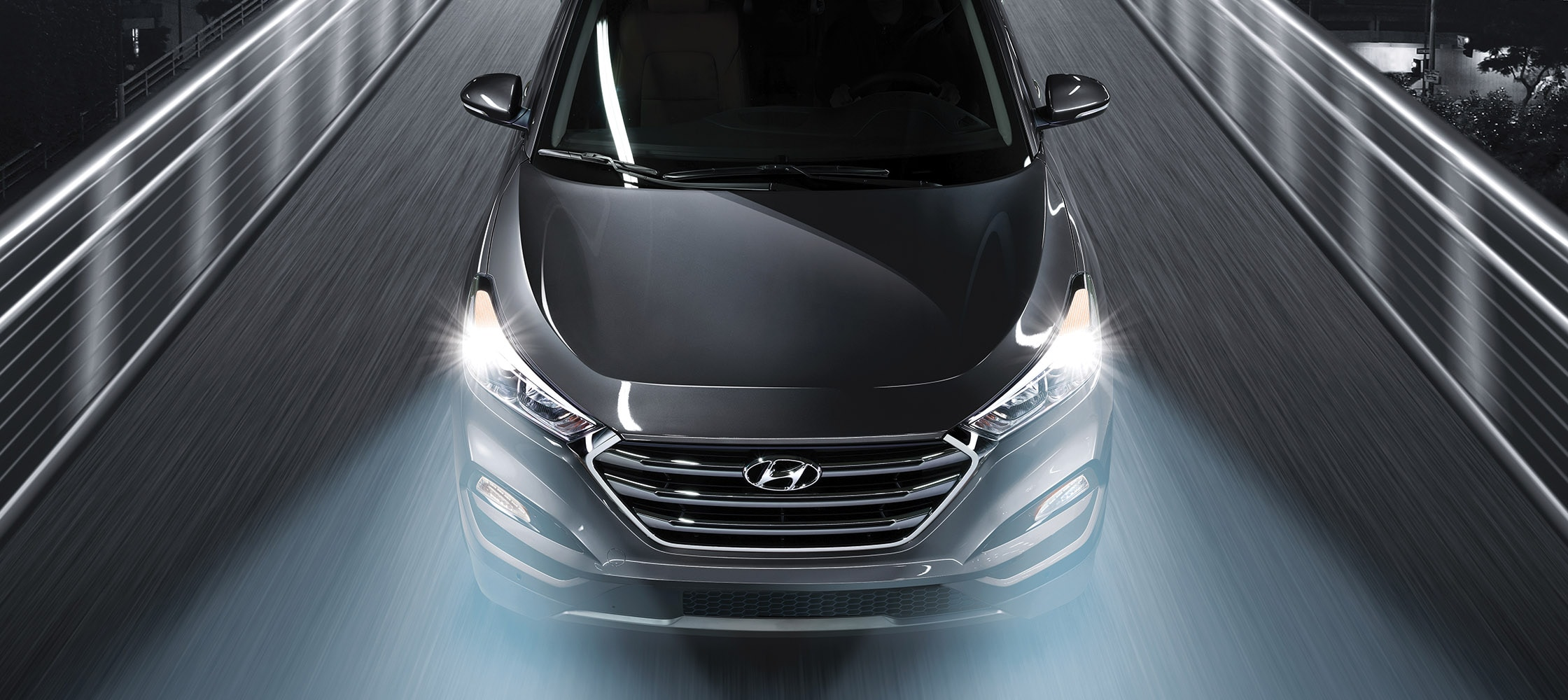 Exterior photo of silver Hyundai Tucson 2017 CUV driving in dark space with bright LED headlights