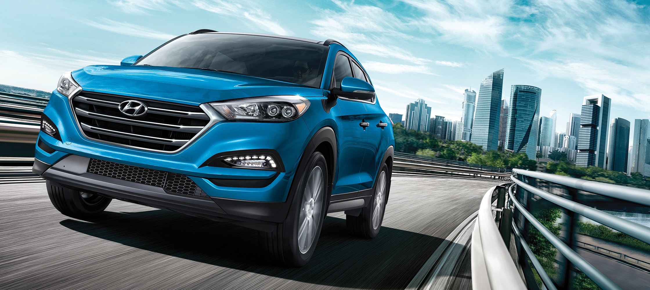 Exterior action photo of blue Hyundai Tucson 2017 CUV with silver lining and tinted windows