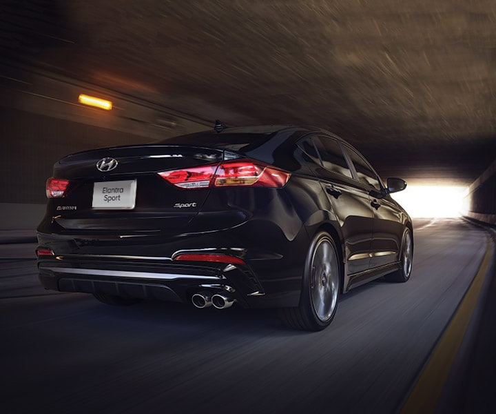 The Hyundai 2018 Elantra sport going through a dark city tunnel depicted from behind
