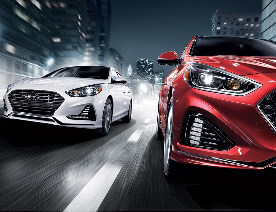 Two 2018 Hyundai Sonatas racing for a city road.