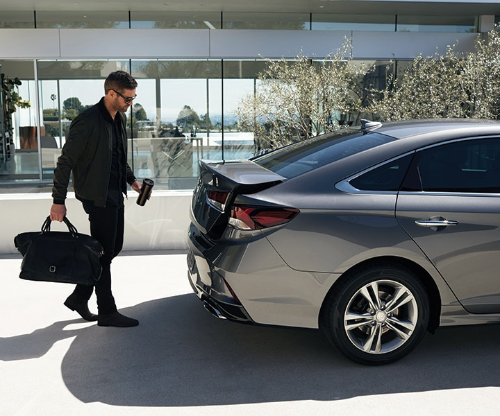Man using the 2018 Sonata hands-free smart trunk to put luggage in the car.