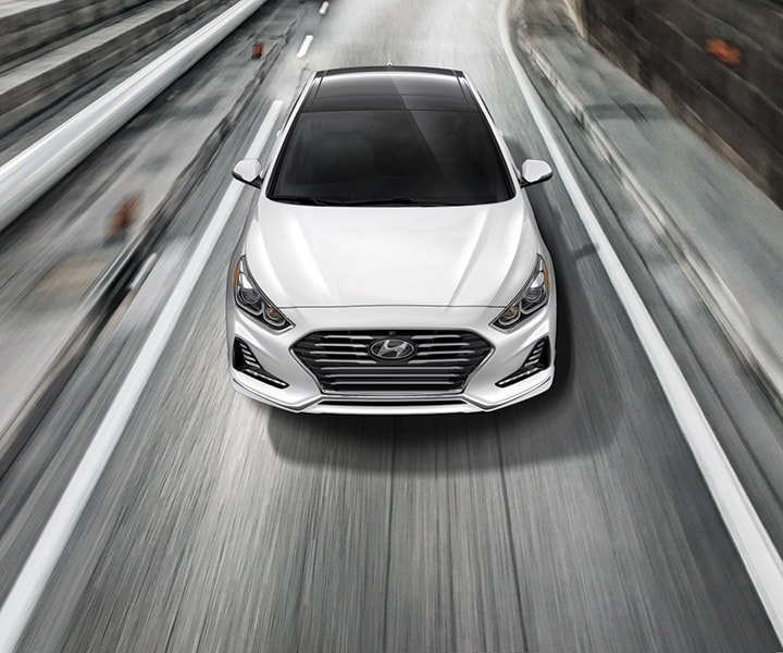 A polar white Hyundai 2018 Sonata driving fast down a city road.