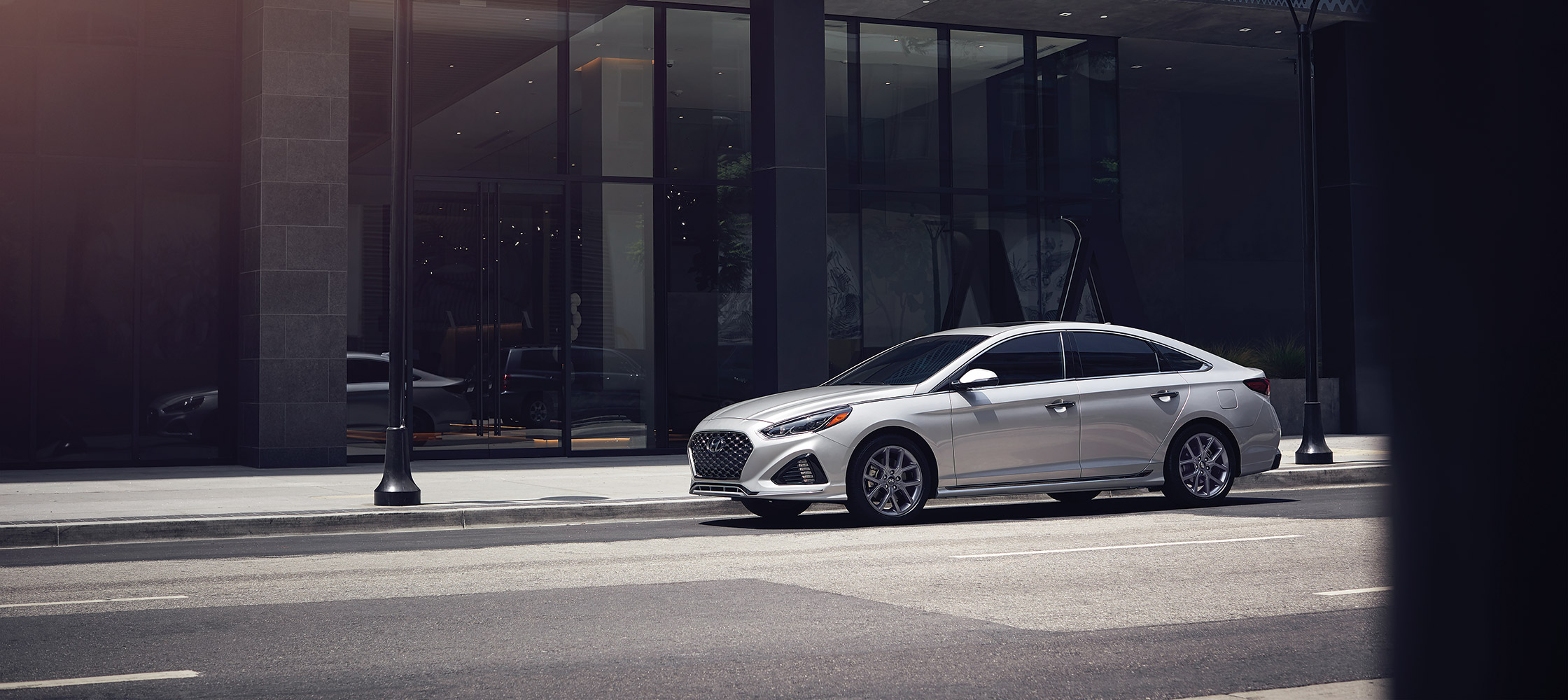 The Hyundai 2018 Sonata in ice white on a city road.