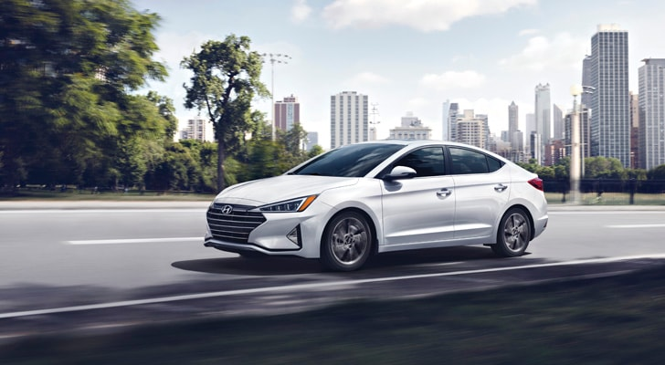 Side exterior view of the 2020 Elantra driving on the road